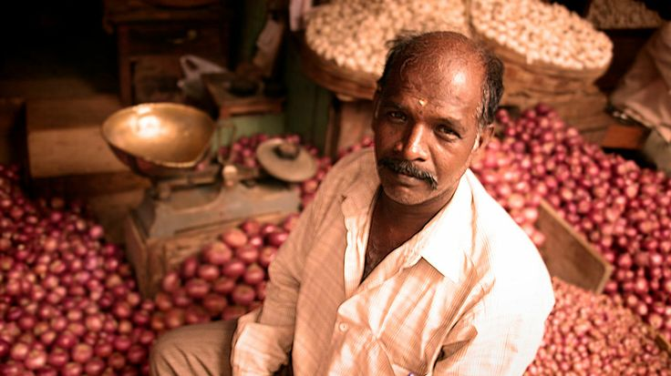 A photograph by photographer Niall O Cleirigh of a man selling red onions he is completely surrounded by them in the Market in Mysore India  www.essentia.ie