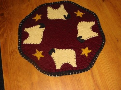 """This is a 9"""" dia. primitive candle mat of my design. The sheep and stars are hand cut and hand sewn. The dark red backing is attached to a black back with a blanket stitch. Enjoy."""