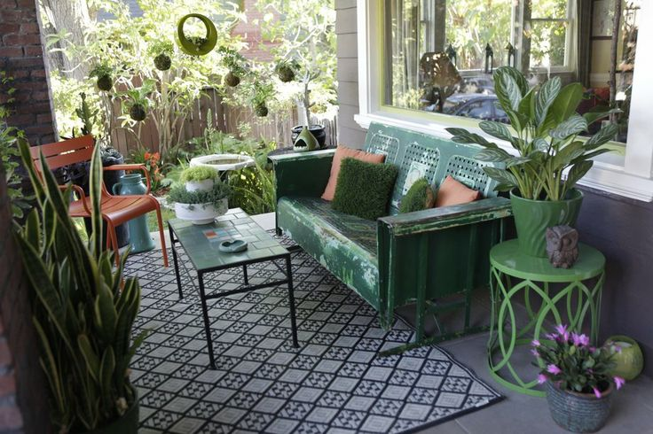 Gutierrez created a living room on her front porch with vintage green seating from the Rose Bowl Flea Market that glides back and forth, a t...
