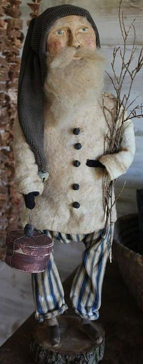 cinnamon creek Santa - 21'' tall standing on his log base. He has a chalkware face, brownish green stocking cap, batting jacket with tiny bell buttons, vintage blue ticking pants