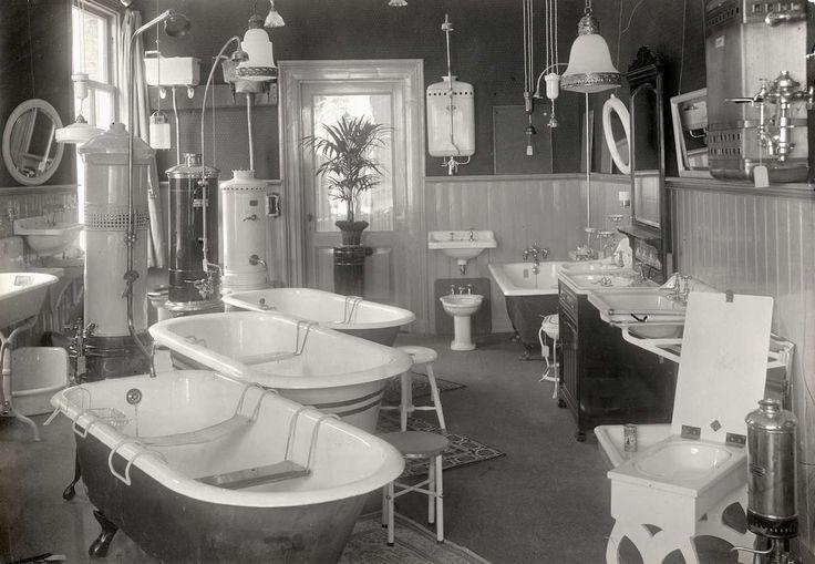 Interieur van winkel in sanitair, kachels en lampen, met oa drie badkuipen prominent in beeld. Nederland, Amsterdam, 1915.