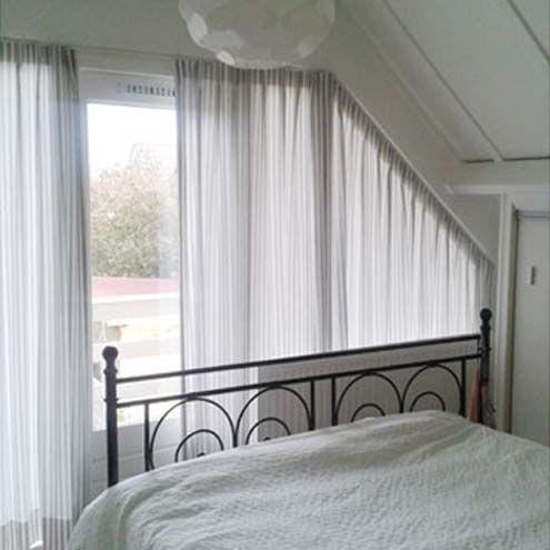gordijneninspiratie - een combinatie van stoer en romantisch geplaatst in een schuin raam