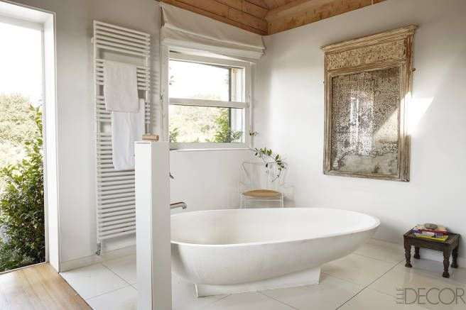 The tub and fittings in the master bath are by Agape, the vintage chair is by Ernest Race, and the antique mirror is French.