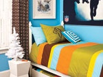 Blue boy's bedroom with football poster, colorful bed linens, brown and white chevron stripe curtains, and shutters