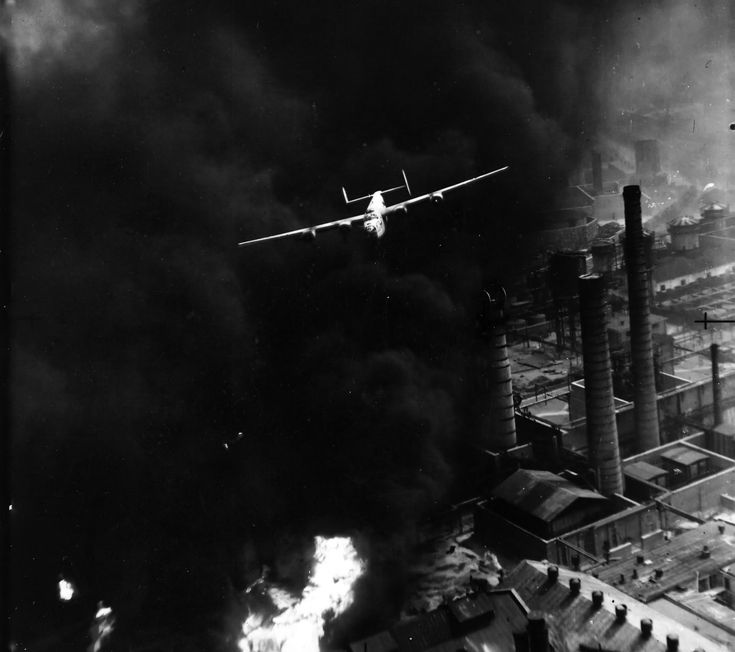 """In one of the most famous images of World War II, the B-24 """"Sandman"""", piloted by Robert Sternfels, emerges from a pall of smoke during Operation Tidalwave, the long distance, low level raid on the Ploesti oil fields in Romania. (August 1, 1943)"""