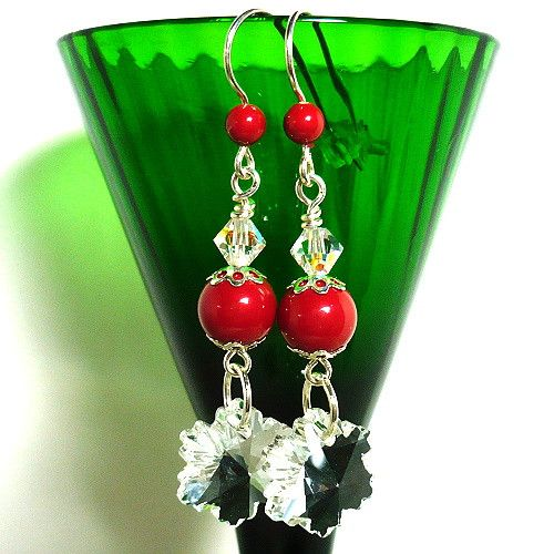 Sparkling sterling silver holiday earrings complete with Swarovski sparkling crystals, Swarovski red crystal pearls and crystal snowflakes will shine from every angle. The star of these Christmas earrings are the laser cut crystal snowflakes with their well defined points which adds a reflection of light and sparkle with every movement. The snowflakes sway dreamily from handmade links using a Swarovski red coral pearls topped with a Swarovski crystal AB bicone. The pop of bright red color on…