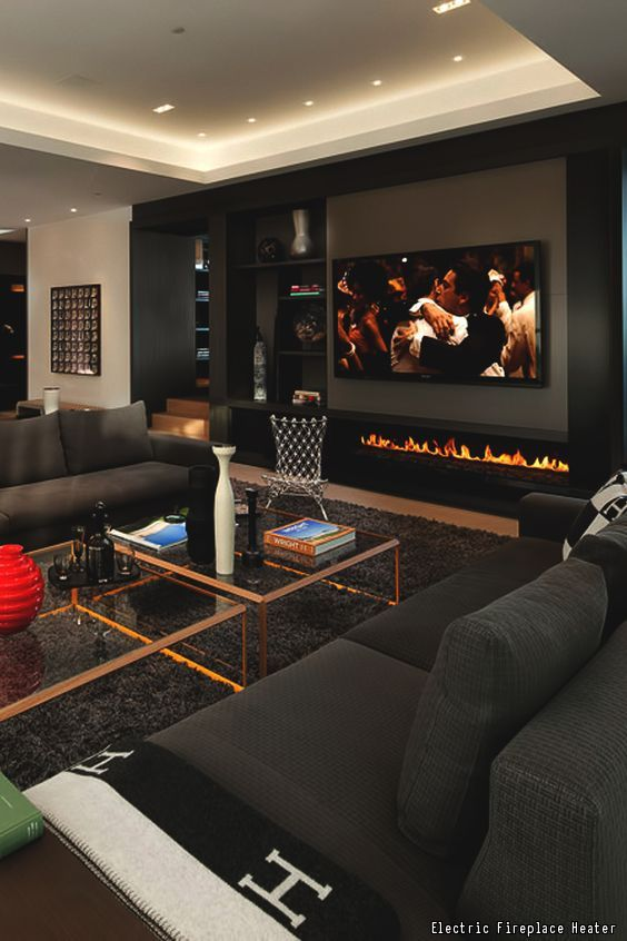 An awesome man cave with comfortable, dark furniture, glass coffee tables and an electric fireplace. Click to see 10 additional must-have items for every man cave.