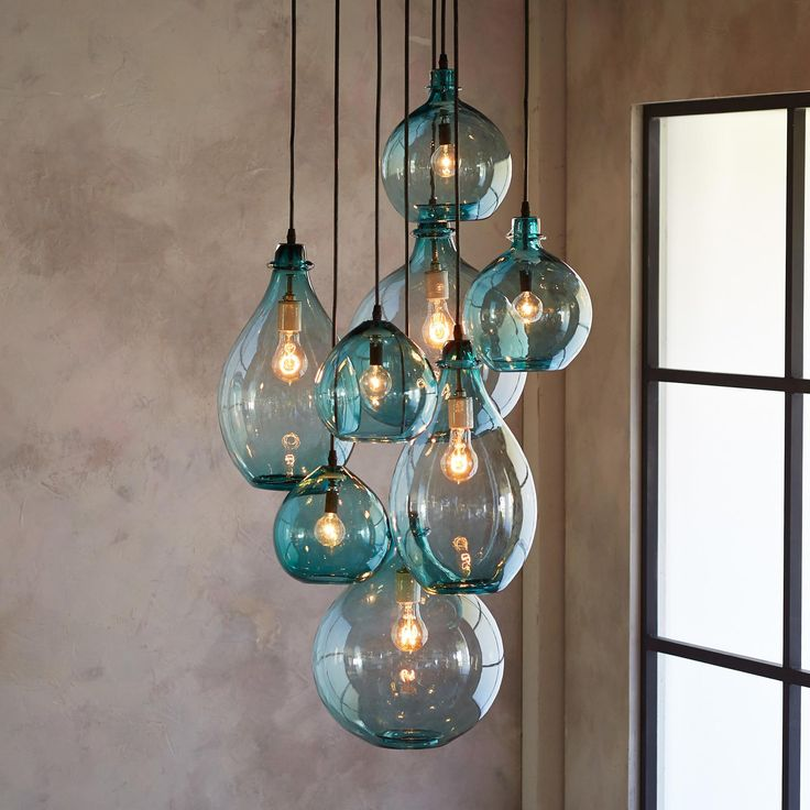 "SALON GLASS PENDANT CANOPY -- Limpid turquoise drops of hand blown glass, envisioned by a Los Angeles artisan Cisco Pinedo, cluster together beneath a hand wrought iron canopy, creating not just lighting but the focal point of any room. Eight lights. Made in USA. 7"" to 20"" dia. x 7"" to 26""H, 100w max. Bulbs not included."