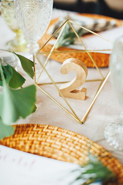 Gold table numbers are luxe accents to otherwise casual decorations | @firstmatephoto | Brides.com