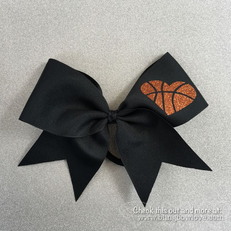 """Show off your love of basketball with this black hoop love bow featuring a glitter heart shaped basketball. 3"""" wide black grosgrain bow with attached nylon pony holder. Bow measures 8"""" x 8"""" with a rib"""