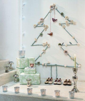 Sapin en branches de bois peintes accrochées au mur et décoré de fleurs en papier et