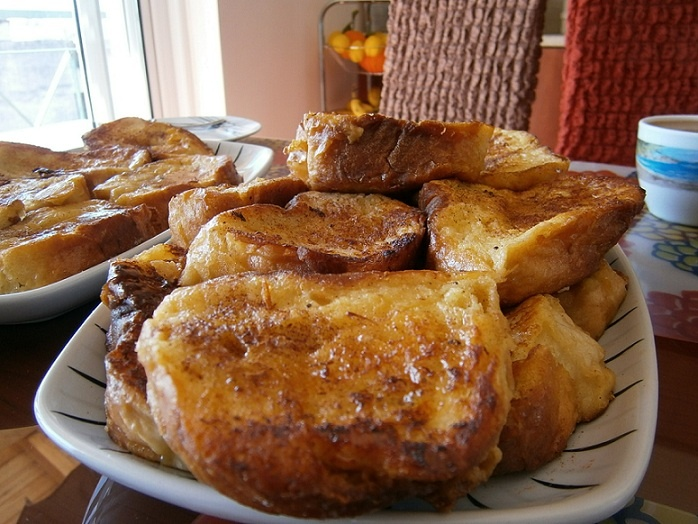 EggBreads - traditional Greek recipe: pieces of bread dipped in milk, then in eggs and then fried in olive oil. Served with honey & cinammon topping.