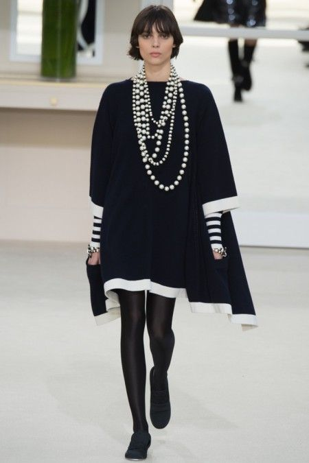 A model walks the runway at Chanel's fall-winter 2016 show wearing a black swing dress with layered pearl necklaces