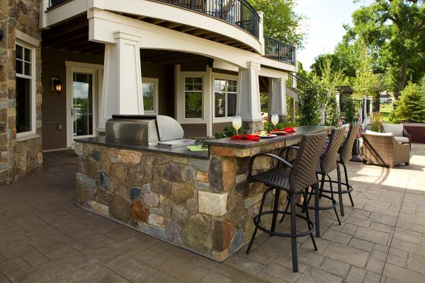 Magnetic Outdoor Kitchen Design Back Yard with Cultured Stone Kitchen Island also Rattan Bar Stools with Backs