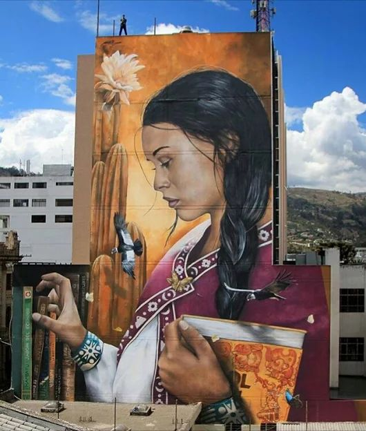 """Entitled """"La Fomule Secrete"""" (The Secret Formula), the mural was painted by Mantra on the National Library's side building wall in downtown Ambato (Ecuador), and depicts a woman in traditional clothes picking up books from the shelf. The artist is trying to convey that knowledge is the best weapon to fight injustice. """"It was rather beautiful the way he put her insecurities to sleep. The way he dove into her eyes and starved her fears, and tasted all the dreams she kept coiled beneath her…"""