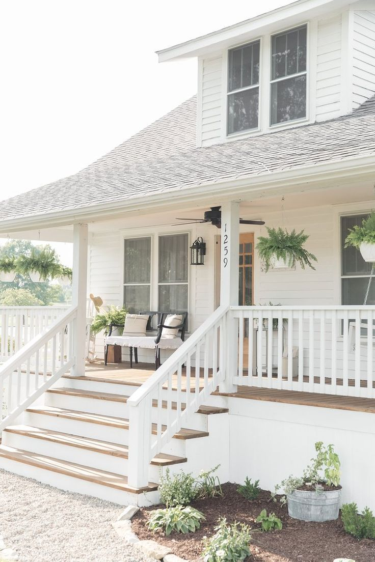 Beautiful wrap around porch, wood stairs, and white siding on this pretty farmhouse