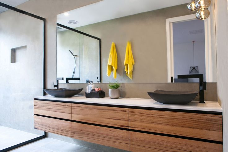 Another image from the striking new display home by Young Gun Builders, Echuca. This unique ensuite boasts a floating timber vanity, stone benchtops and contemporary above-counter stone basins. The use of black shower screens in this space complements our matte black swivel mixers and portable shower head perfectly!