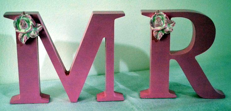 Letra Decorativa com apliques <br> <br>As letras decorativas são feitas em MDF, pintadas à mão e com colocação de figuras, nesta peça foi aplicado Flores em Resina, mas fazemos com qualquer motivo. <br>Apliques em gesso/resina em diversos motivos, consulte-nos. <br> <br>Temos todas as letras do alfabeto, consulte-nos! <br> <br>As letras ficam em pé perfeitamente sem apoio. <br> <br>Tamanho: <br>- 15 c de altura x 15cm de comprimento x 2,5cm de largura. <br> <br>Fica lindo para decorar mesa…