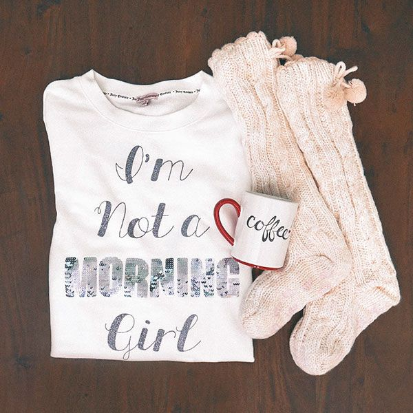 """You know the type. She just needs an hour or so and a cup of coffee or two to fully wake up. The perfect gift for your favorite sleepyhead includes a pajama top which reads everything anyone around her should know—""""I'm not a morning girl"""" —and an adorable coffee mug. We threw in the cozy slipper socks for good measure (and great comfort)."""