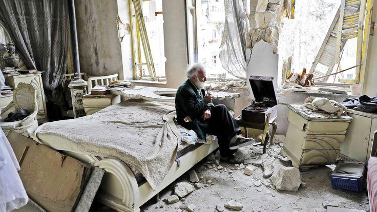 En gammel, hvithåret mann sitter med snadden sin og lytter til klassisk musikk fra en platespiller i et sønderbombet soverom. Bildet fra Aleppo går nå verden rundt.