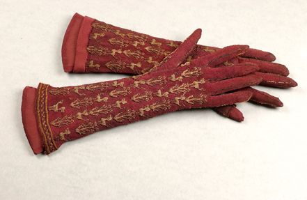 A pair of purple knitted silk ladies gloves, probably Italian, late 17th century, elbow length, worked in gold with repeats of stylised beasts and flower stems, 35 cm long. Part of the Collection donated to the Livery in 1959 by the late Robert Spence.