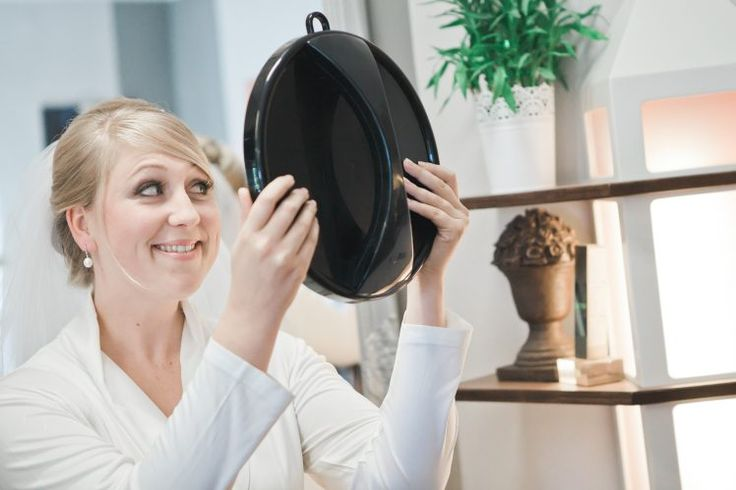 Bride checking hairstyle in mirror.