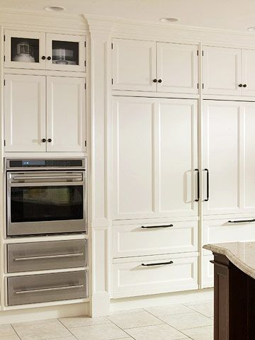 Sturdy Elegance: Surprise Inside The wall of white cabinetry conceals the oversized refrigerator & freezer, creating a streamlined look. Recessed panels on cabinets add depth  Placing a standout element, such as the stainless steel oven  drawers, within wall-to-wall cabinetry helps break up the space without being intrusive.