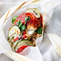 Ryba pieczona w papilotach z cukinią, pomidorami i ajvarem
