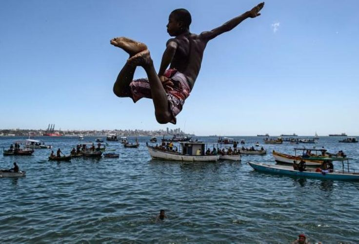Un joven se lanza a la playa de Viagem en Salvador Bahía en Brazil.