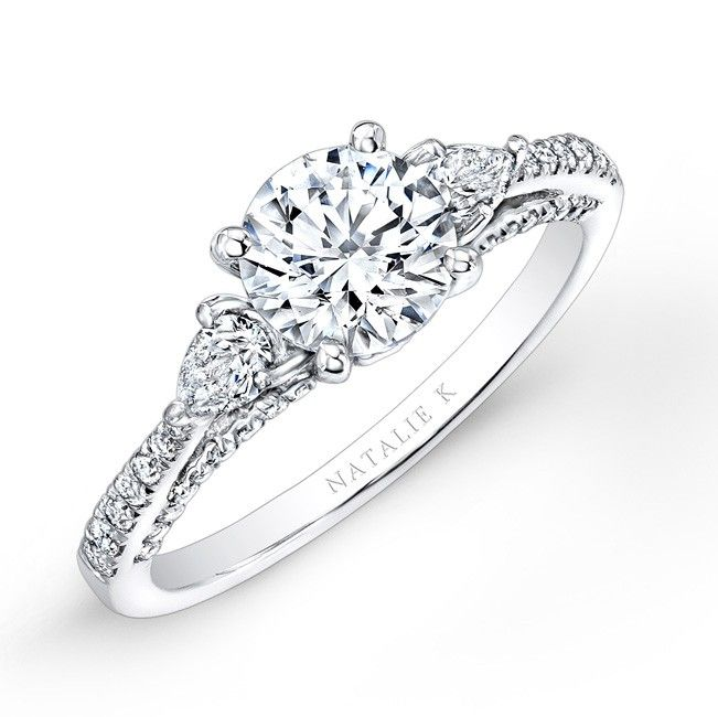 Natalie K - Pear shaped white diamonds sit on either side of a center mounting that sits about a diamond encrusted gallery in this beautiful three stone diamond engagement ring.