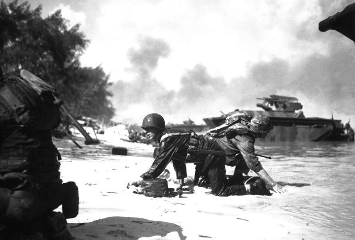 Two US Marines crawling into position on a Saipan Mariana Islands beach after their landing craft was hit by Japanese mortar 15 June 1944.