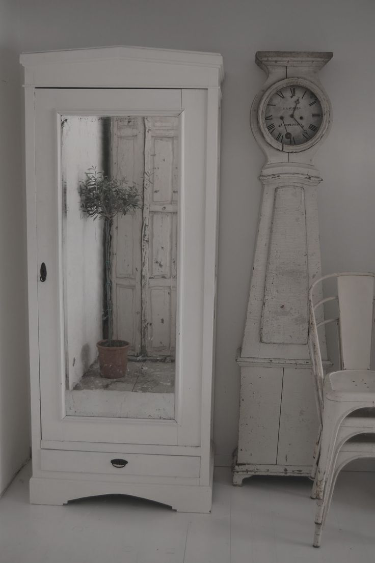 Armario ropero vintage blanco con especo. No es un armario grande y se encuentra en el dormitorio pequeño del piso. Se encuentra cerca de la cama y a lado hay un reloj y algunas sillas en estilo vintage también.
