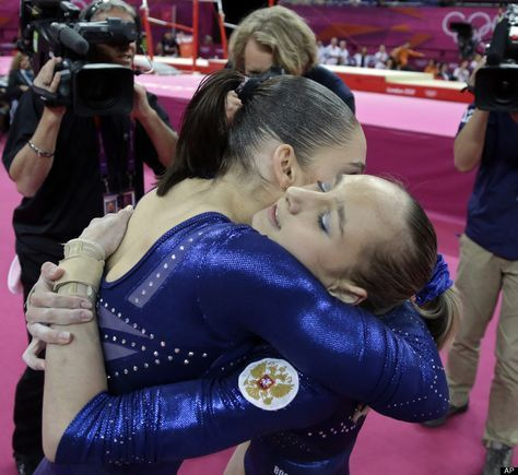 Russian gymnast Aliya Mustafina, left, and teammate Victoria Komova hug each other and wait for the declaration of results during the artistic gymnastics women's individual all-around competition at the 2012 Summer Olympics, Thursday, Aug. 2, 2012, in London.