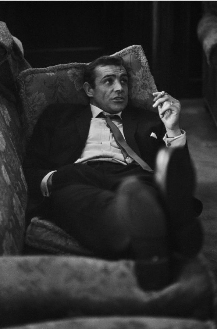 A young Sean Connery relaxing on the couch.