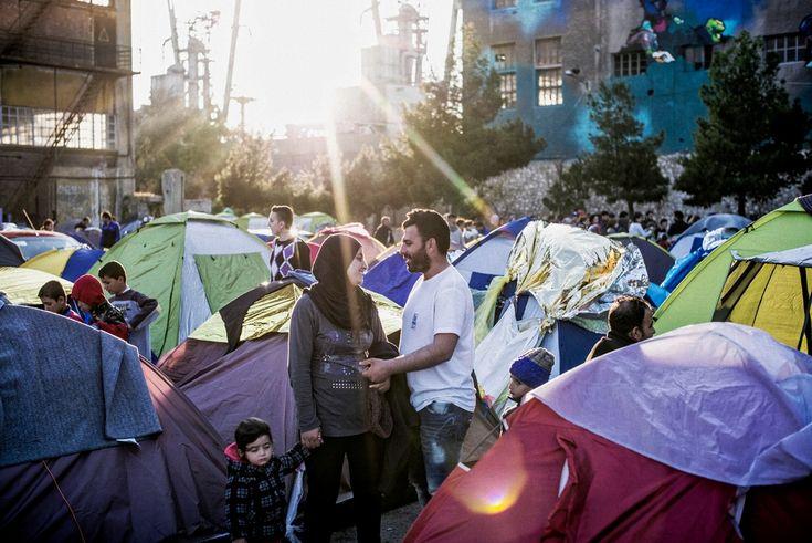 Μάρτιος 2016: Ζευγάρι μοιράζεται μια στιγμή στη λιακάδα στον αυτοσχέδιο καταυλισμό προσφύγων που στήθηκε στη σκιά των αποθηκών στο λιμάνι του Πειραιά. Περίπου 5.000 άνθρωποι που σκόπευαν να ταξιδέψουν στη βόρεια Ευρώπη εγκλωβίστηκαν στην Αθήνα όταν η ΠΓΔΜ έκλεισε τα σύνορά της τον Μάρτιο.