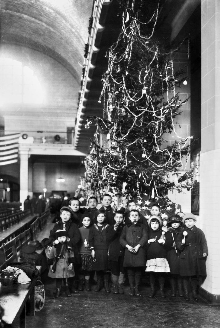 ELLIS ISLAND: CHRISTMAS, 1920. Group of immigrant children photographed in front of a Christmas tree inside the registry room at Ellis Island, New York City.