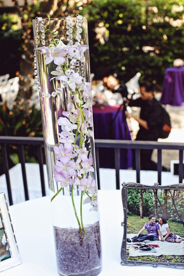 Centro de mesa con base cilindro alta y flores orquídea dendrobium lila y piedras