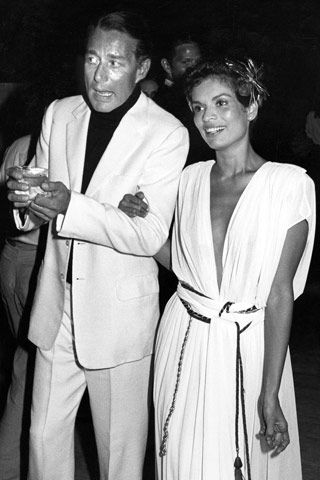 Roy Halston started as a hat designer. He designed the pillbox hat for Jacqueline Kennedy, went on to perfume and clothing in the 70's. Was a regular at Studio 54. Pictured here with Bianca Jagger.