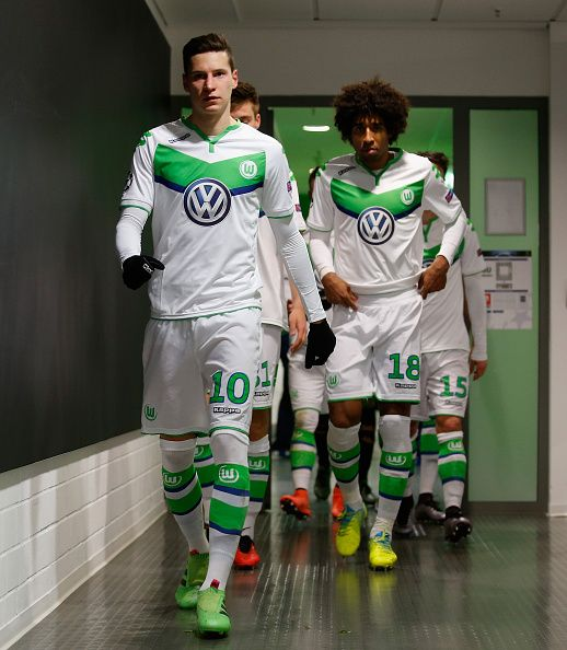 Julian Draxler and Dante of Wolfsburg come to enter the pitch at halftime during the UEFA Champions League round of 16 second leg match between VfL...