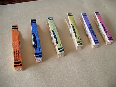 "Cute way to hang kids' art:  decoupage crayon wrappers to wood clothespins, hang heavy twine ""clothesline"" onto a wall with push pins, and clip the art onto the line with these cute crayon pins!"