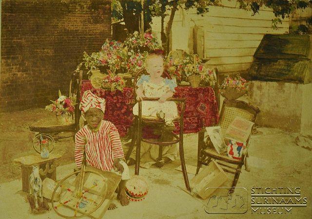 Eerste verjaardag van Maurits Lens, 1 juli 1892. Ingekleurde foto. Let op de persoon onder de tafel die de kinderstoel vasthoudt. En dit, lieve mensen, is precies 29 jaar NA de afschaffing van slavernij! Ongelooflijk!