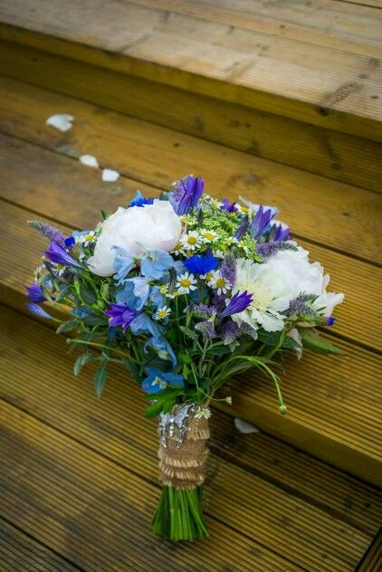 Vintage style bridal bouquet of blue and white country style flowers, including peonies, cornflowers, delphinium, brodea, ammi, mentha, scabious and feverfew.