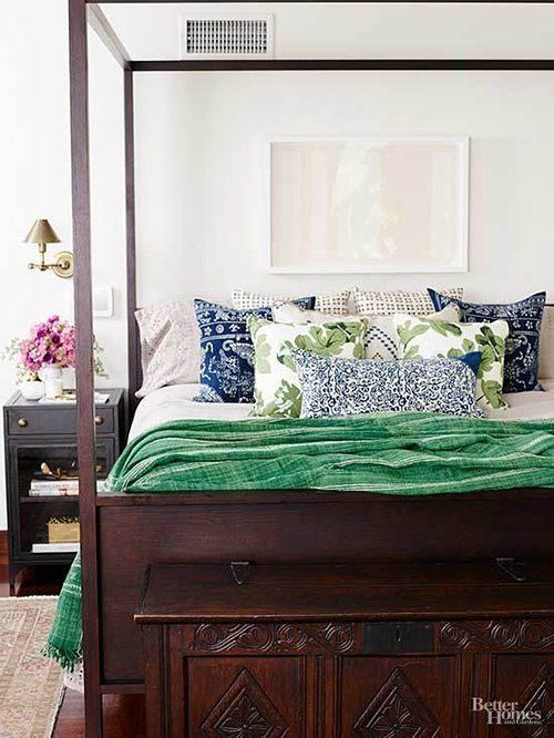 A carved wooden four-poster bed with green coverlet, dark brown bedside tables, metal wall sconce and colorful patterned pillows.