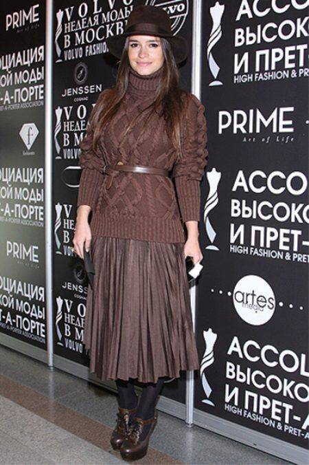 Mira Duma in brown chunky sweater, accordion pleat skirt with belt, hat & boots