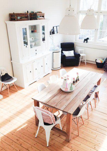Combinación de sillas Eames y Tolix blanca en la cabecera de una mesa de tablones de madera en dirección opuesta a los tablones de madera del parquet
