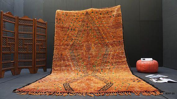 Deze oranje en rode Beniourain tapijt is handgeknoopte door Berberse vrouwen in de dorpen rond Khnifra met natuurlijke wol vezels gekleurd met natuurlijke verfstoffen. De kleur is suggestief van de gebouwen en waterkwalitiet beniourain regio en de bodem van het aangrenzende land.