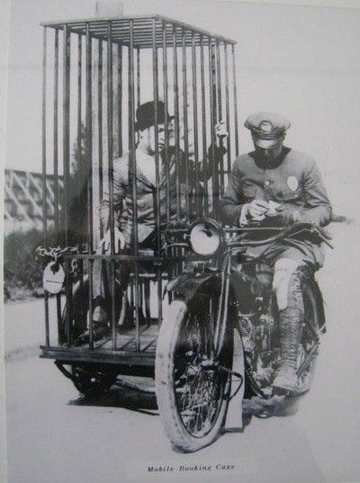 A police officer on a Harley and an old fashioned mobile holding cell (1921)
