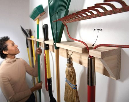 Build a wooden yard tool hanger if you are the handy type.  Simple and inexpensive.