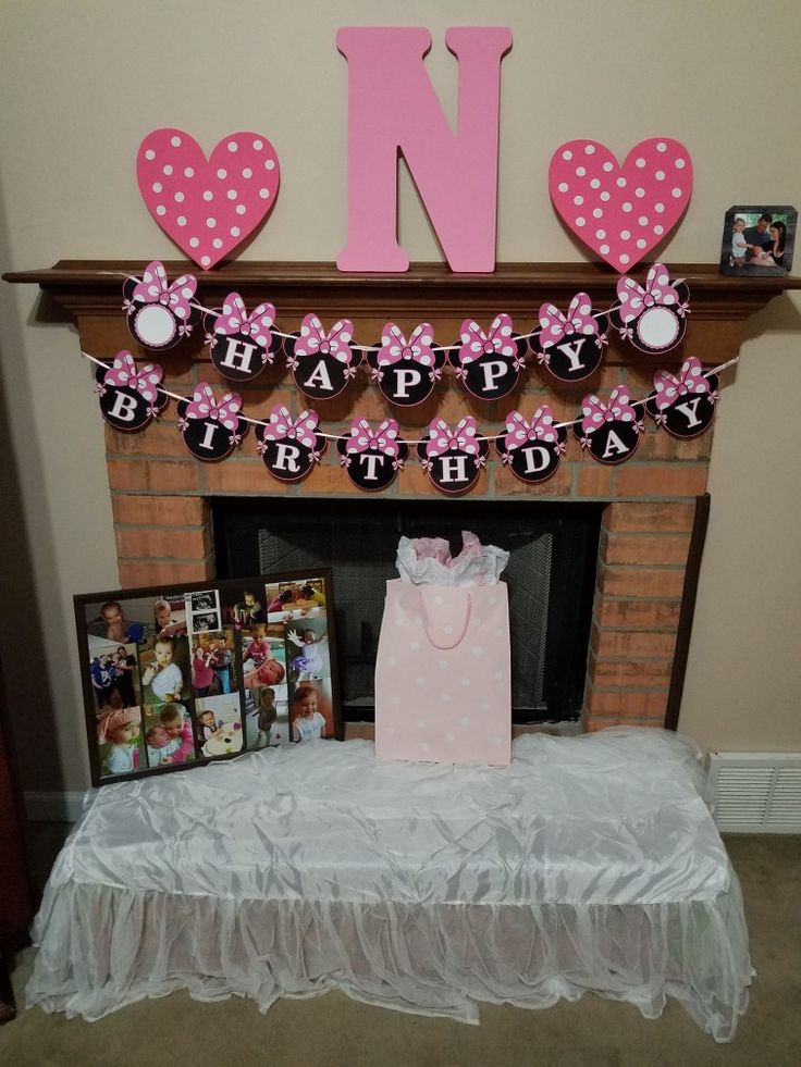 This sign from Amazon made  the area for presents. Used the N from the baby shower, tulle crib skirt to cover the fireplace bumpers, put white dot labels on our present to her and leftover Valentine ❤ decorations, and put up a bunch of cute photos of my baby on an old board with glue dots.