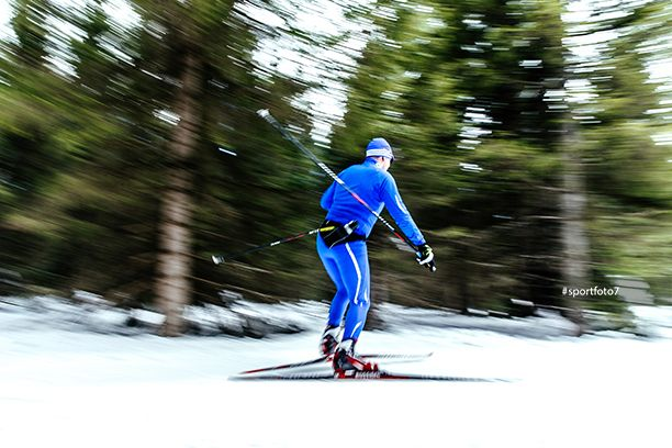 blurred image male skier athlete pine forest snow trail